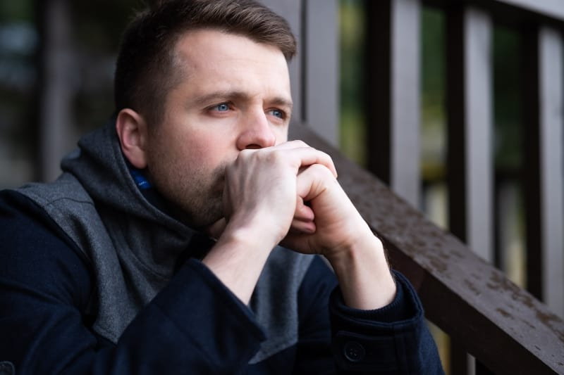 Der traurige Mann sitzt alleine und denkt nach