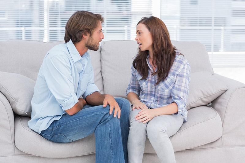Junges Paar, das im Therapeutenbüro spricht, während es auf der Couch sitzt