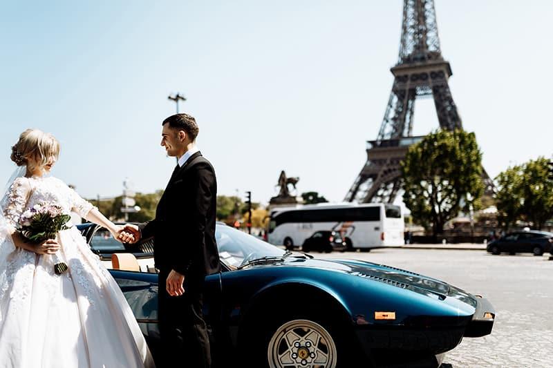 Jungvermählten in Paris in der Nähe des Autos stehen