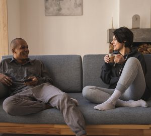 glückliches Liebespaar, das auf der Couch sitzt und spricht