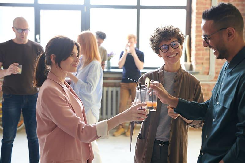 Kollegen, die auf einer Firmenfeier einen Toast mit Getränken trinken