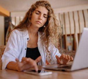 Eine besorgte Frau überprüft ihr Telefon, während sie vor dem Laptop sitzt