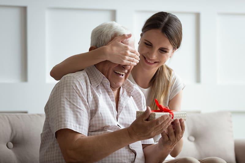 Lächelnde Frau, die reife Vateraugen bedeckt, während sie ihm ein Geschenk gibt