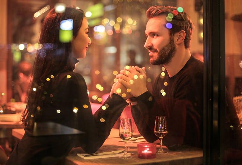 Liebespaar Händchen haltend beim Sitzen im romantischen Restaurant