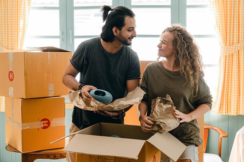 Liebespaar packt Sachen aus den Kartons in der Wohnung aus