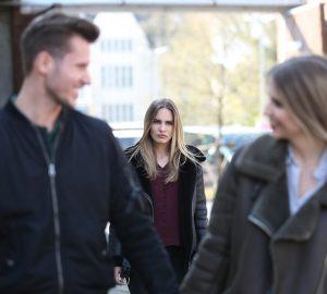 verärgerte Frau, die einen Ex-Freund und eine andere Frau ansieht, während sie hinter ihnen geht