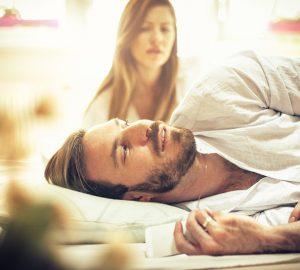 Ein Mann versteckt das Telefon vor seiner Frau, während er im Bett liegt