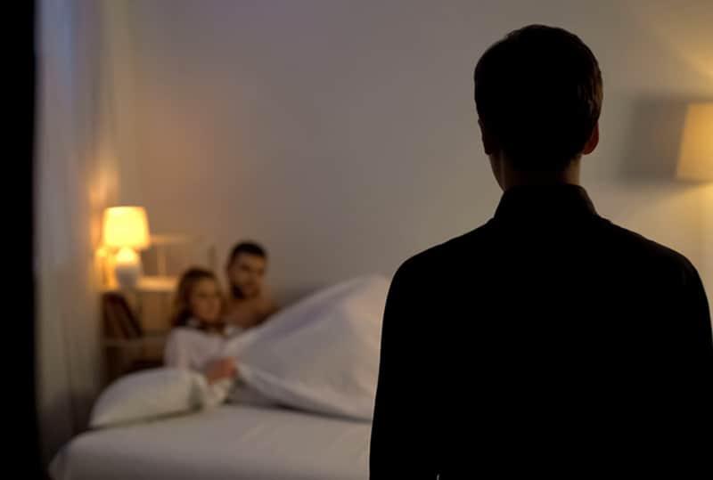 Mann, der seine Frau mit Liebhaber im Bett betrachtet, während er an der Tür steht