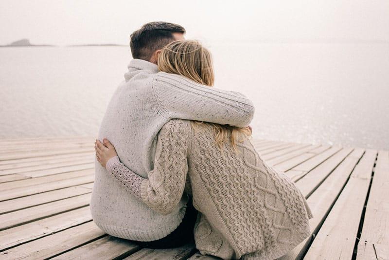 Mann umarmt Frau auf dem Pier