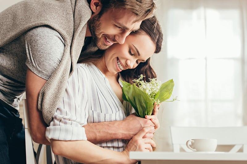 Mann umarmt eine Frau von hinten und hält einen Blumenstrauß, während sie am Tisch sitzt
