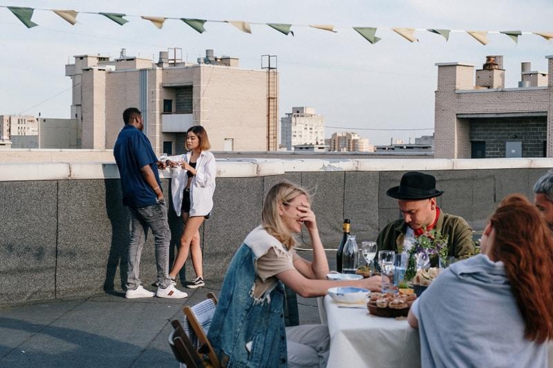 Mann und Frau flirten, während sie getrennt von Freunden auf einer Party auf einem Dach stehen