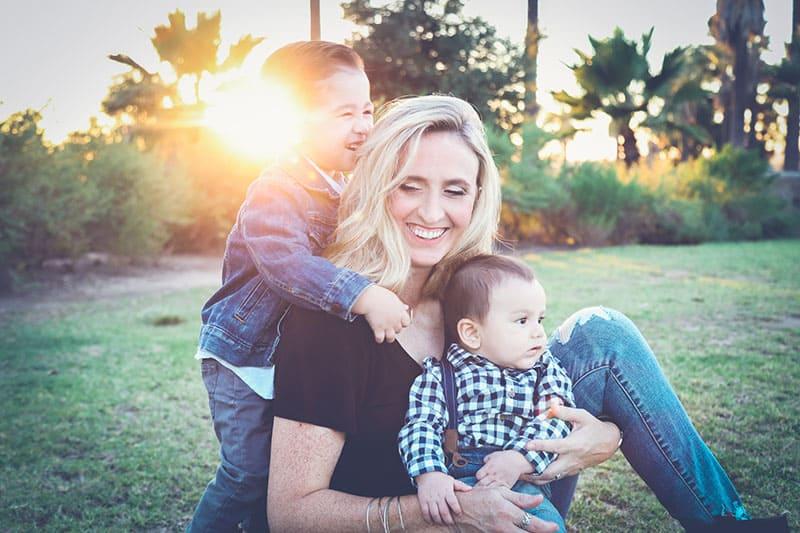 Mutter sitzt mit ihren Kindern im Gras
