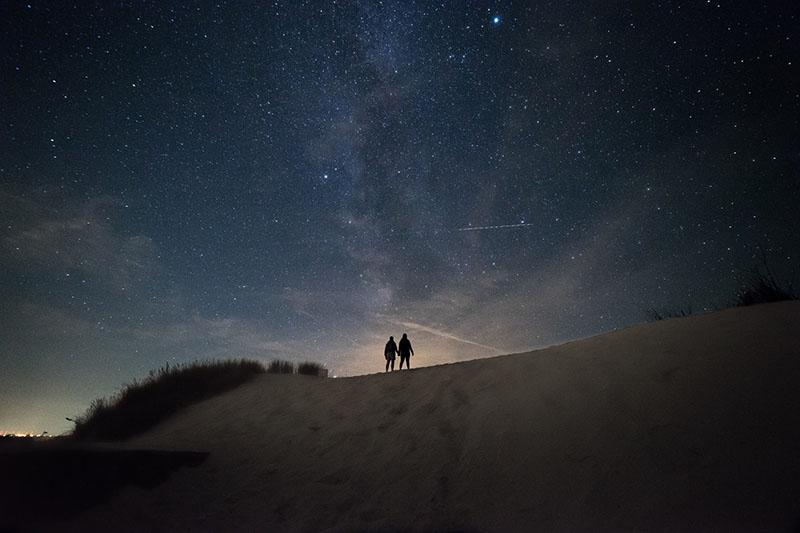 Paar, das unter dem Sternenhimmel geht