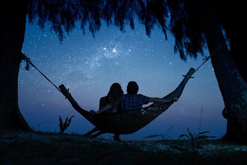 Paar, das sich in einer Hängematte entspannt und den Sternenhimmel genießt