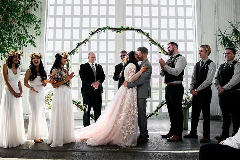 Paar küsst sich auf ihrer Hochzeit mit Brautjungfern und den Trauzeugen