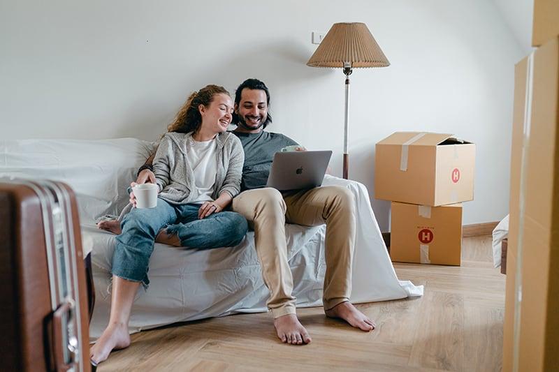 Paar sitzt auf der Couch und schaut auf einen Laptop beim Umzug in eine Wohnung