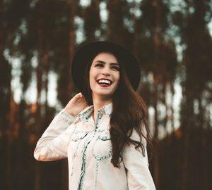 lächelnde Frau mit Hut im Park stehend