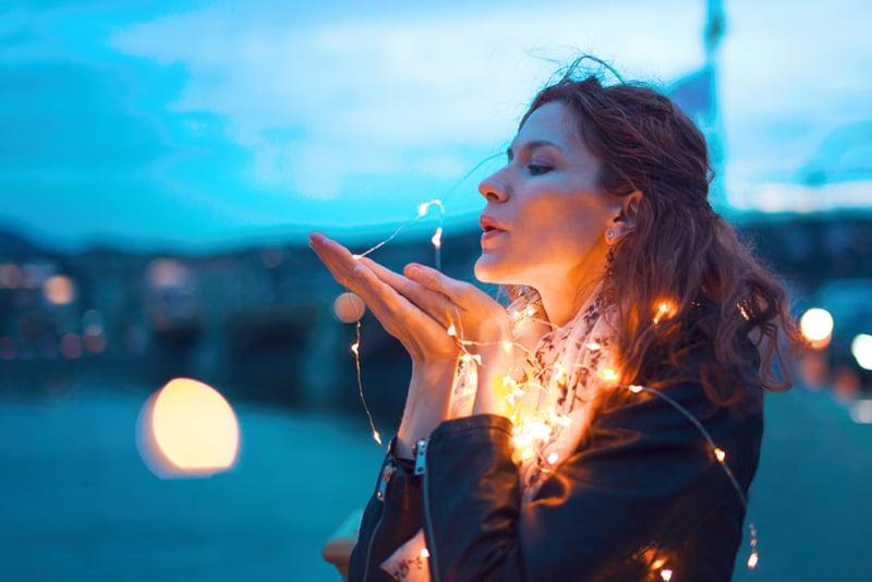 Rothaarige Frau, die nachts Kuss mit Lichterkirlandin sendet