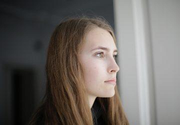 eine nachdenkliche Frau, die durch das Fenster schaut