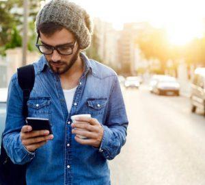 Ein Mann ging die Straße entlang und hielt ein Handy in den Händen.jpg – prečac