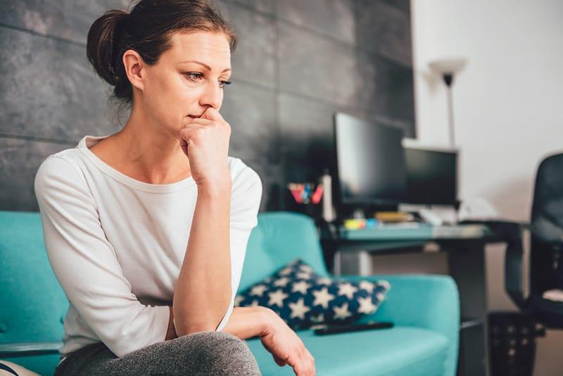 Traurige Frau, die auf einem Sofa im Wohnzimmer sitzt