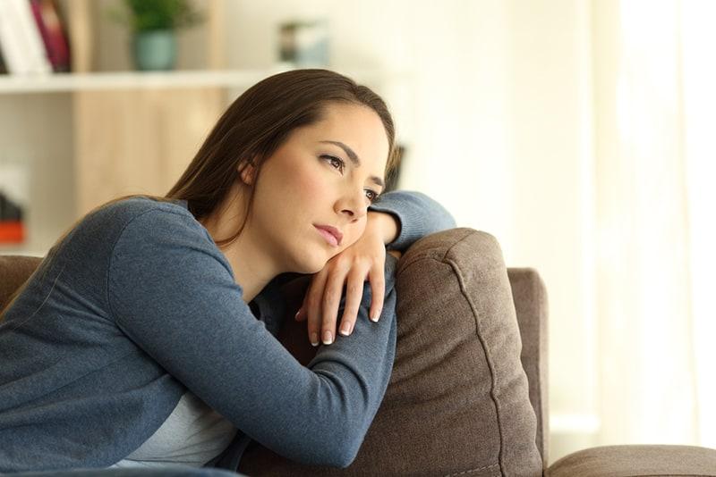 Traurige Frau, die durch ein Fenster schaut, das auf dem Sofa sitzt