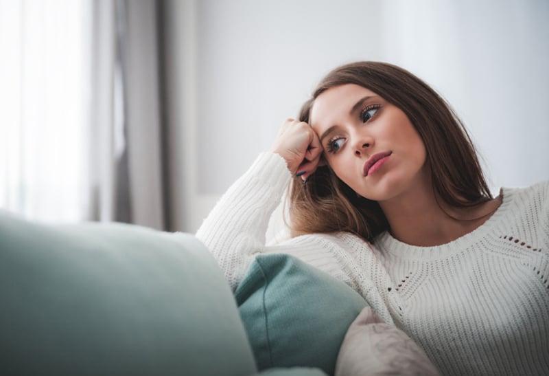 Traurige Frau, die tief in Gedanken auf dem Sofa zu Hause sitzt