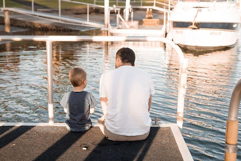 Vater sitzt mit seinem Sohn auf dem Pier