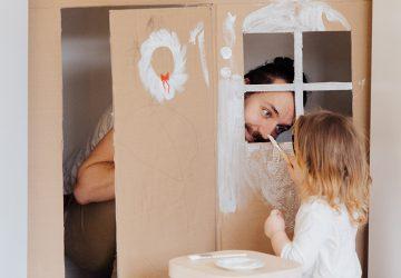 Ein Vater spielt mit seiner kleinen Tochter in einem Kartonhaus