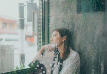 Ein trauriges junges Mädchen sitzt am Fenster, als der Regen fällt.jpg – prečac