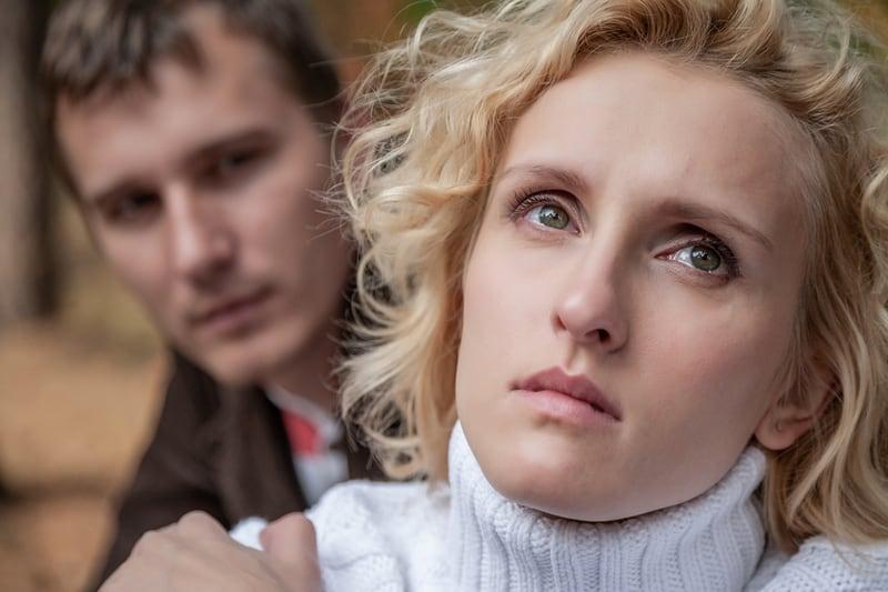 Eine traurige Frau schaut auf und setzt sich zu einem Mann