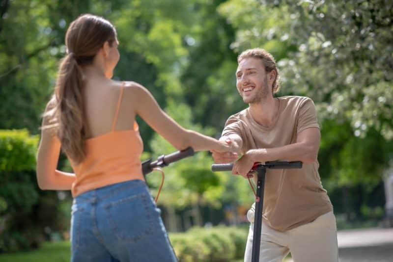 Im Park trifft ein lächelnder Mann eine Frau