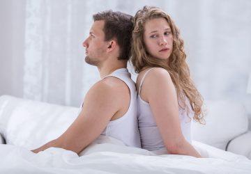 Ein Mann und eine Frau lehnen sich mit dem Rücken aneinander, während sie auf dem Bett sitzen