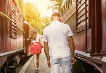 eine Frau, die von einem Mann abreist, der zwischen Zügen steht