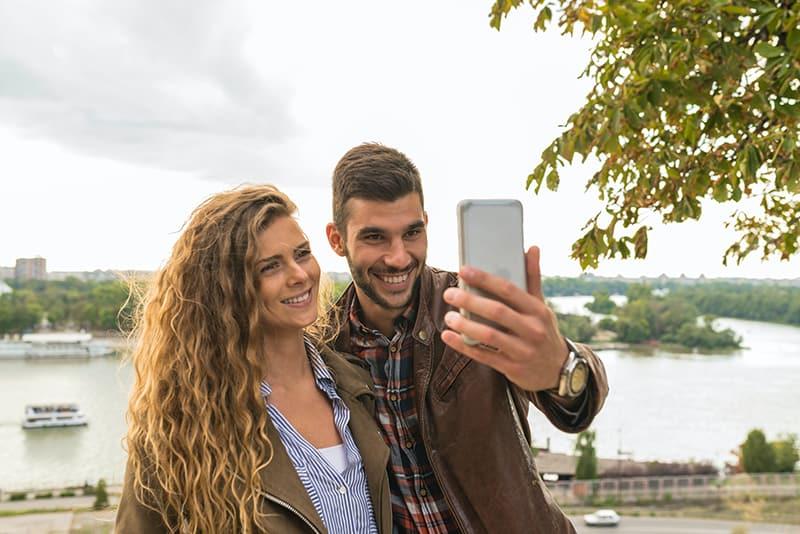 Ein lächelnder Mann und eine Frau machen ein Selfie mit einem Smartphone