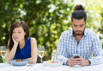 Ein Mann ignoriert eine Frau und benutzt ein Handy in einem Restaurant