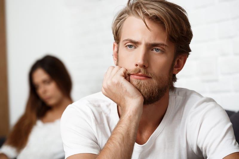 bärtiger Mann denkt nach, während seine Freundin hinter ihm sitzt