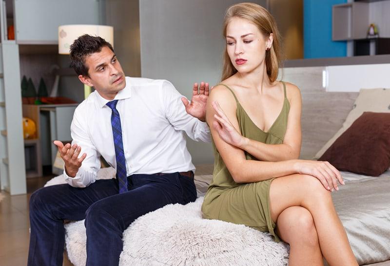 beleidigtes Mädchen, das auf dem Bett sitzt und ihrem Mann genug mit der Handfläche gestikuliert nach einem Streit