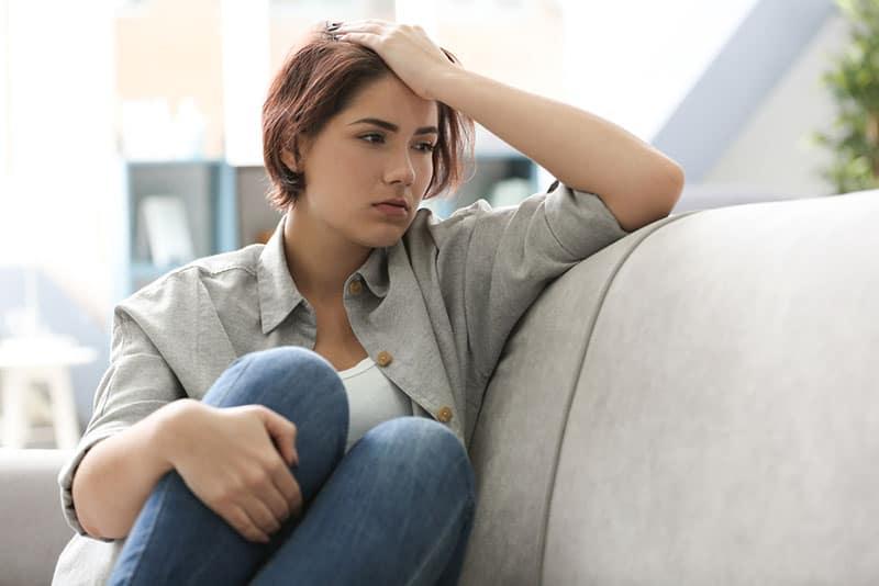 besorgte Frau, die achtsam auf der Couch sitzt
