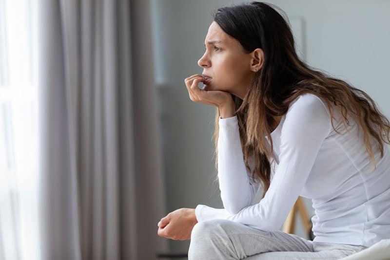 besorgte Frau, die auf Distanz schaut und wartet