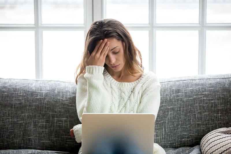 besorgte Frau sitzt auf der Couch mit Laptop