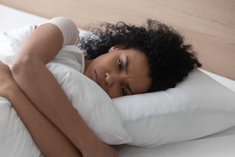 besorgte achtsame Frau im Bett liegen