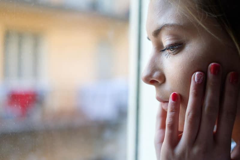 besorgte junge Frau am Fenster stehen