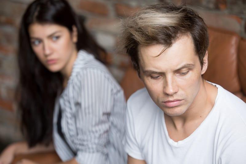 depressiver trauriger Mann, der nach unten schaut, während er neben seiner Freundin auf der Couch sitzt