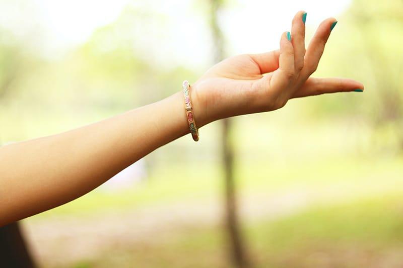 die linke Hand einer Frau mit Armband darauf