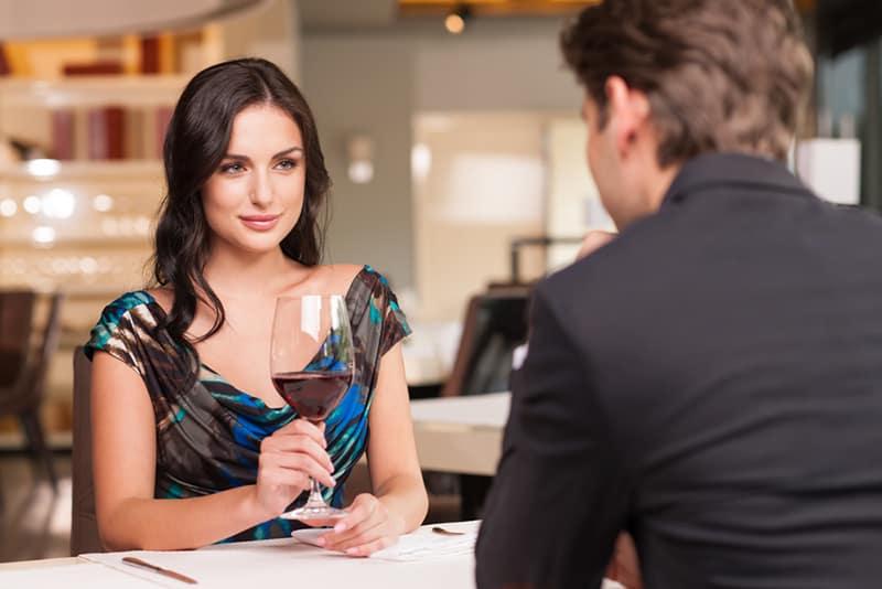 dominante Frau, die einen Mann betrachtet, der über ihr sitzt und ein Glas Wein hält
