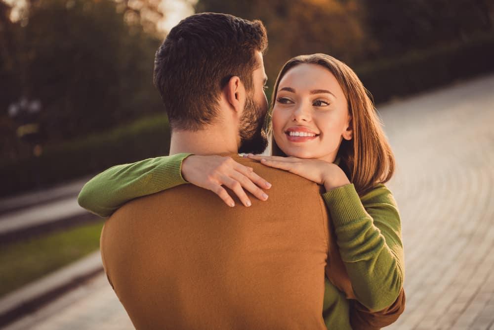 draußen steht in den Armen einer schönen Frau und eines Mannes mit Bart