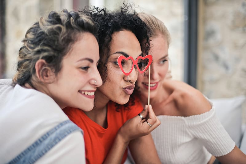 Drei Freundinnen posieren für das Foto, während sie auf der Couch sitzen