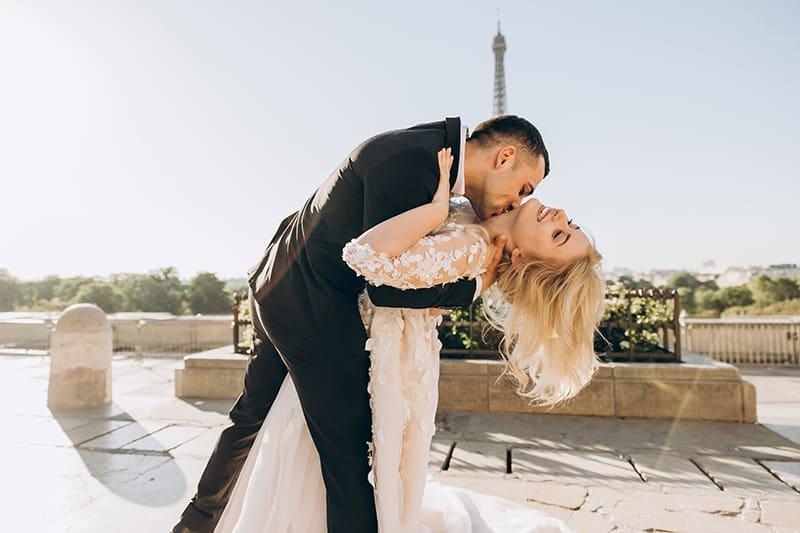 Ein Bräutigam küsst den Brauthals, während er sie in seinen Armen hält