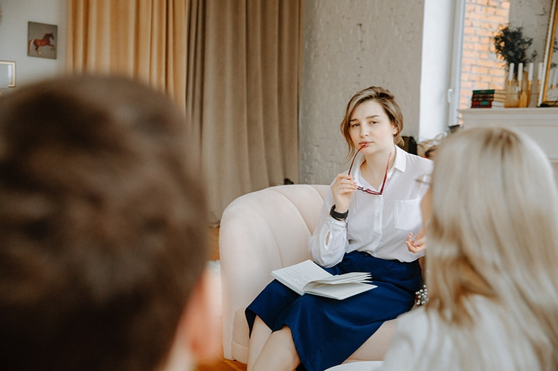 ein Eheberater, der im Sessel sitzt und Ehepaar betrachtet